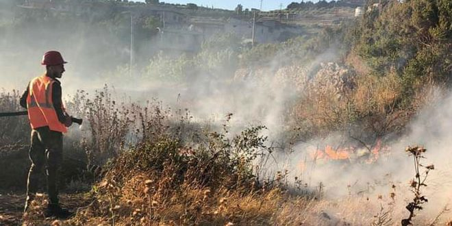 Firefighters are working to extinguish fire that broke out in agriculture crops in Homs countryside