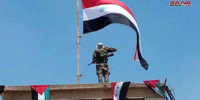Izada bandera nacional siria en el municipio de Bousra Al-Sham en Deraa