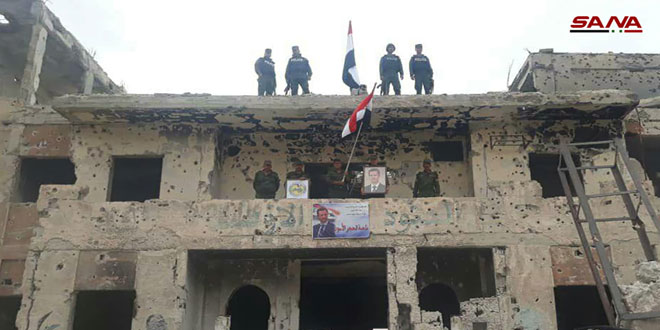 Fuerzas de Seguridad Interna izan la bandera nacional siria en Hayyar Asswad