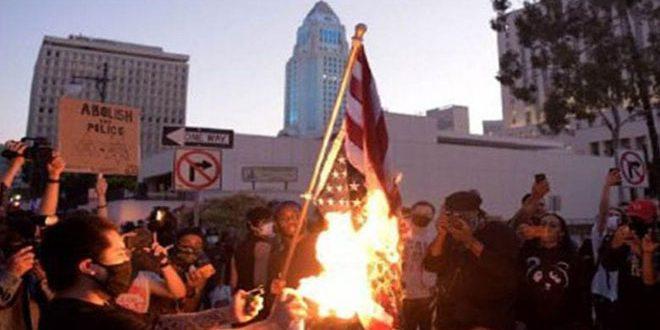 מוחים מציתים הדגל האמריקאי סמוך לבית הלבן אחרי נאומו של טרמפ