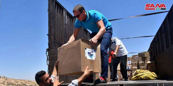 توزيع مساعدات روسية للمهجرين بمركز الإيواء في مدينة حسياء الصناعية